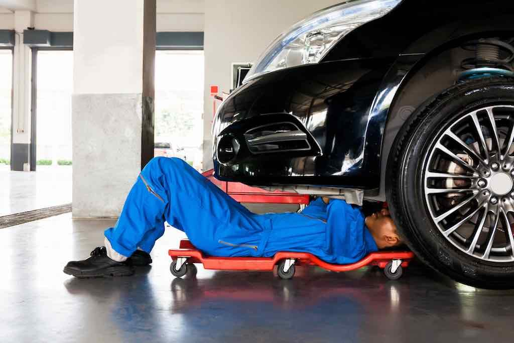 Mechanic in blue uniform lying down and working under carservice garage